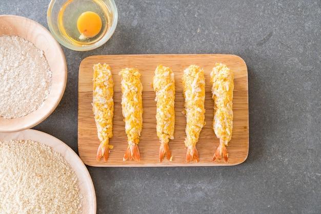 Broodgebakken garnalen op houten bord