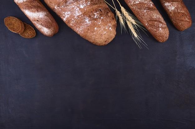 Broodgrens op hout met exemplaar ruimteachtergrond. bruine en witte volkoren broden stillevensamenstelling met tarwe oren verspreid rond. bakkerij en supermarkt voedsel winkel concept.