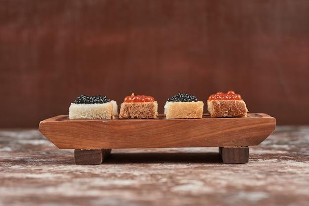 Broodhapjes op marmer met kaviaar.