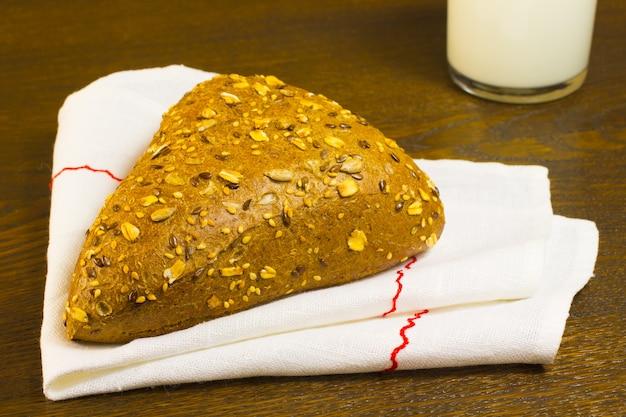 Broodje bestrooid met sesamzaadjes op een wit servet en een glas melk