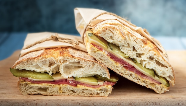 Broodje ciabatta met krokant korstje, mosterd, ham, kaas, augurk op een houten dienblad