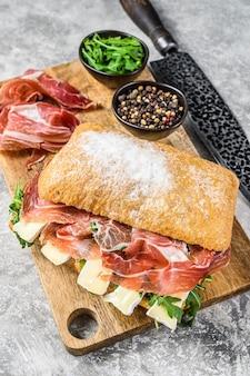 Broodje ciabatta met prosciutto crudo ham, rucola en camembert brie. grijze achtergrond. bovenaanzicht.