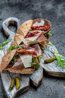 Broodje ciabatta met prosciutto, zongedroogde tomaten, augurken, parmezaan en rucola. verticaal beeld. bovenaanzicht