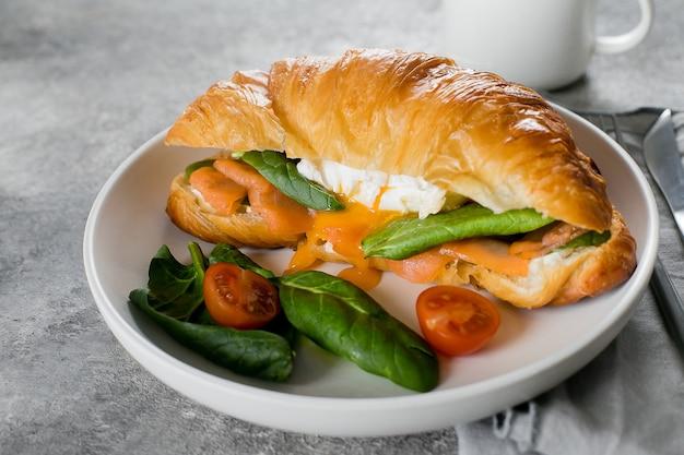 Broodje croissant met kwark, zalm, spinazie en gepocheerd ei in een bord in