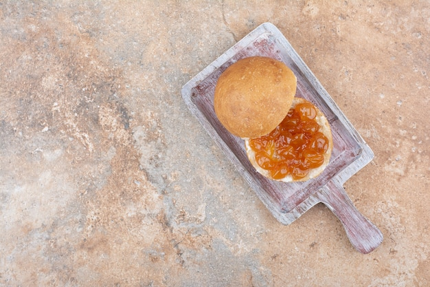Broodje en bessenjam op houten bord