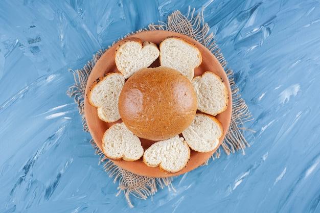 Broodje en gesneden brood op plaat op jute servet op blauw.