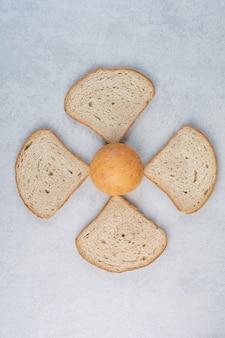 Broodje en sneetjes brood op marmeren achtergrond. hoge kwaliteit foto