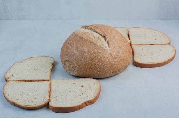 Broodje en sneetjes roggebrood op marmeren achtergrond. hoge kwaliteit foto