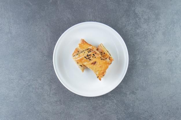 Broodje gevuld met vlees op witte plaat.