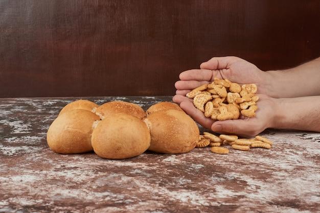 Broodje in de hand van de bakker met crackers.