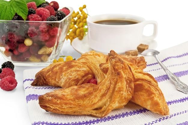 Broodje in het gestreepte servet, frambozen, bramen, aardbeien in een glazen kom, koffie in een witte kop, lepel, boerenwormkruid bloemen geïsoleerd op een witte achtergrond