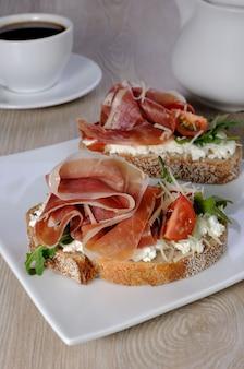 Broodje jamon met ricotta, rucola, kaas en een plakje kers