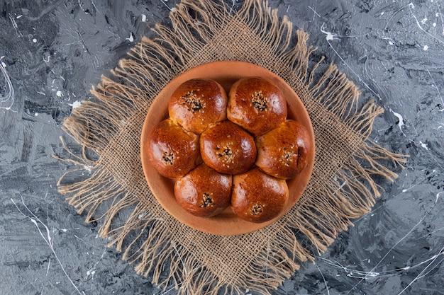 Broodje kamille met maanzaad op een kleiplaat