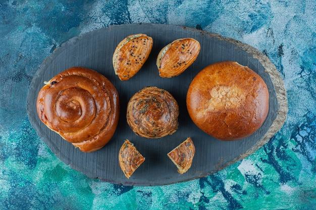 Broodje, koekje en kaasgebak aan boord, op de marmeren tafel.