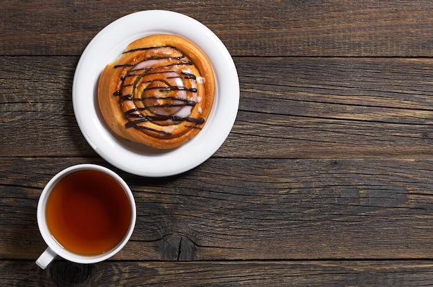 Broodje met chocolade en kopje thee op oude houten