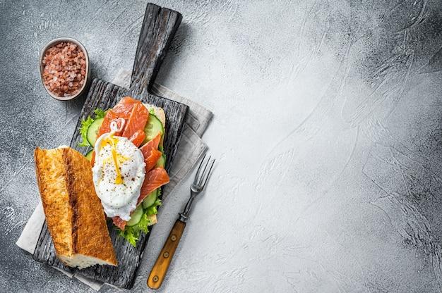 Broodje met gepocheerd ei, gerookte zalm en avocado op toast. witte achtergrond. bovenaanzicht. ruimte kopiëren.