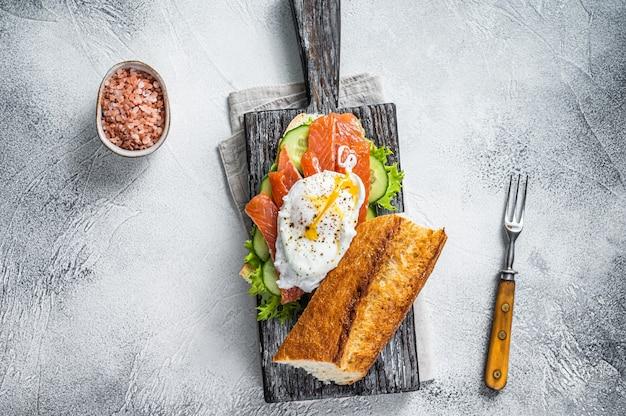 Broodje met gepocheerd ei, gerookte zalm en avocado op toast. witte achtergrond. bovenaanzicht.