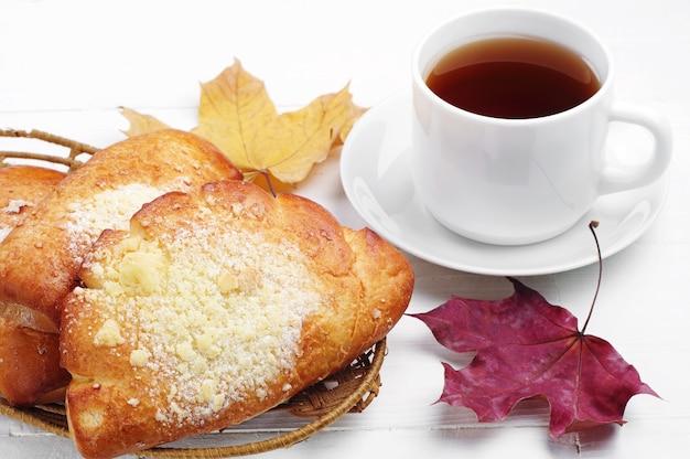 Broodje met kopje thee en esdoorn bladeren op witte tafel