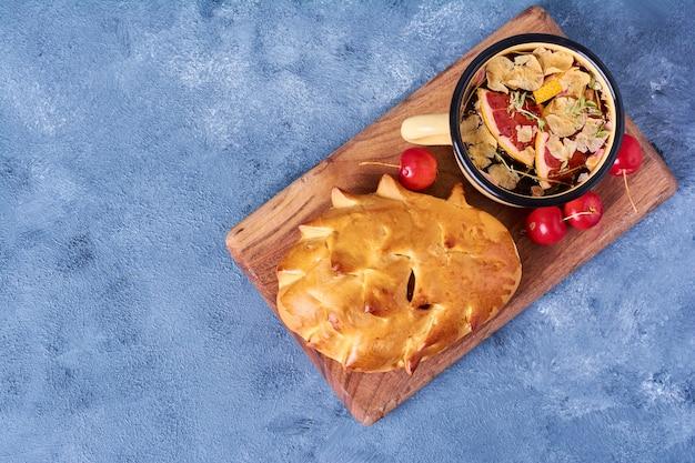Broodje met kruidendrank op een houten bord op blauw