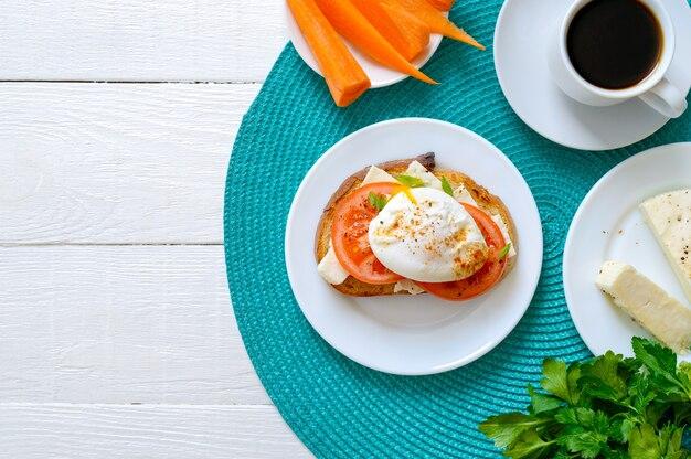 Broodje met volkoren brood, geitenkaas, verse tomaten en gepocheerd ei. heerlijk eenvoudig ontbijt. goede voeding. bovenaanzicht, plat lag, kopieer ruimte.