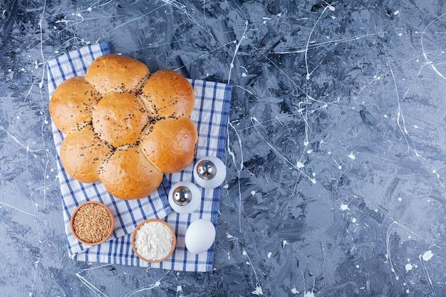 Broodje met zwarte zaden met een wit kippenei en bloem op een tafelkleed.