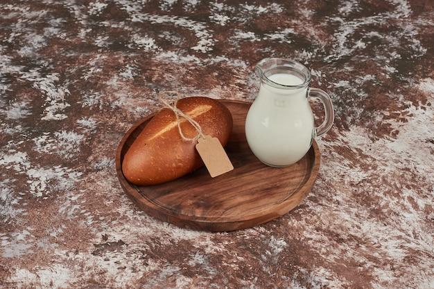 Broodje op marmer op een houten bord met een potje melk.