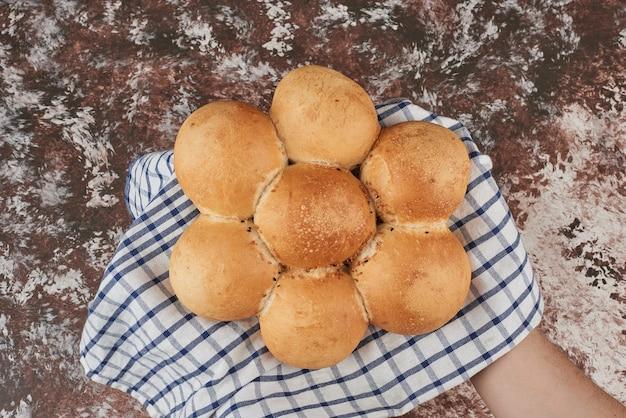Broodje op marmer op geruite handdoek.