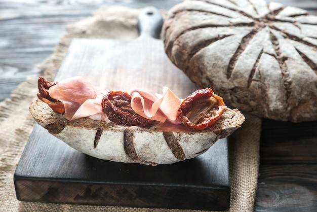 Broodje roggebrood met ham en zongedroogde tomaten