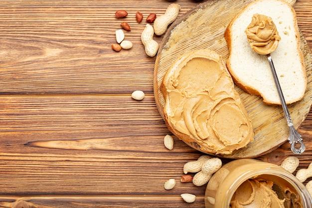 Broodje toast met pindakaas. lepel en pot pindakaas en pinda's voor het koken van ontbijt op een bruine houten achtergrond. romige pindapasta plat lag met plaats voor tekst.