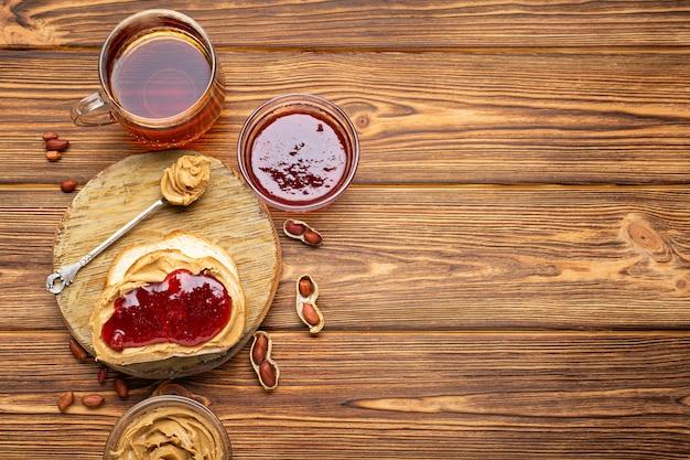 Broodje toast met pindakaas. lepel en pot pindakaas, jam, kopje thee en pinda's voor het koken van ontbijt op een bruine houten achtergrond. romige pindapasta plat lag met plaats voor tekst.