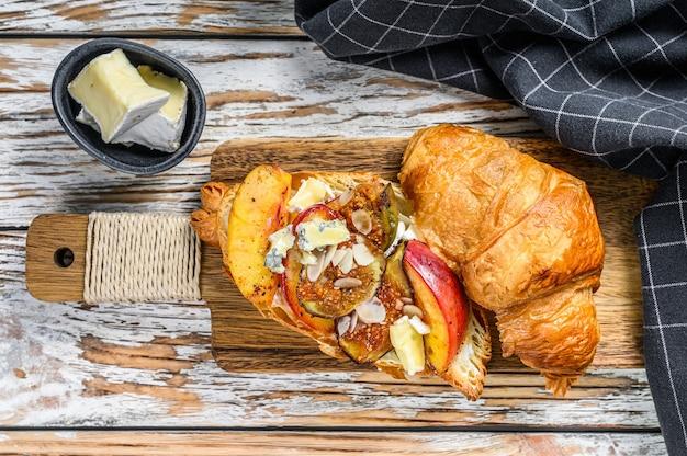 Broodje verse croissants met brie kaas, perzik en vijgen. heerlijk ontbijt. bovenaanzicht.
