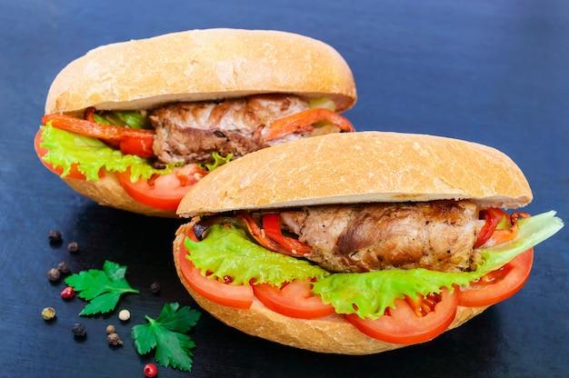Broodje vleesrolletjes met groenten in een broodje met tomaat en slablaadjes