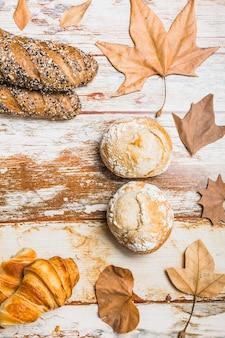 Broodjes en bladeren in de buurt van vers brood