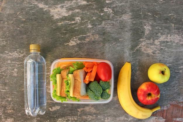 Broodjes, fruit en groenten in voedseldoos, water op oude houten ondergrond. bovenaanzicht. plat leggen.