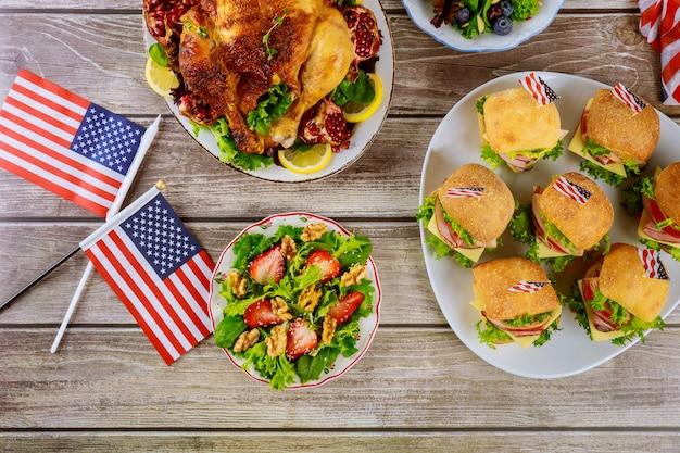 Broodjes, kip en salade op houten tafel