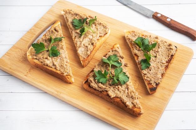 Broodjes knapperige toast en kippenleverpastei met peterseliebladeren op een houten snijplank. ruimte kopiëren.