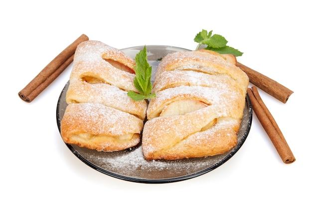 Broodjes met appel, kaneel en munt bestrooid met poedersuiker op een plaat op wit