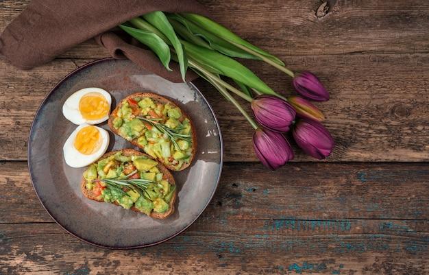 Broodjes met avocado, eieren en tulpen op een houten achtergrond. het concept van feestelijke culinaire achtergronden.