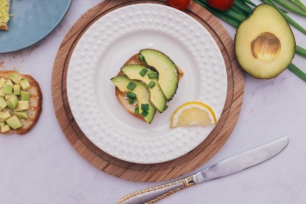 Broodjes met avocado, tomaten en kruiden op een houten achtergrond op tafel. concept van gezond eten en vegetarisme, het juiste ontbijt voor een goede spijsvertering.