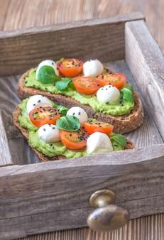 Broodjes met avocadopasta, kerstomaatjes en mozzarella