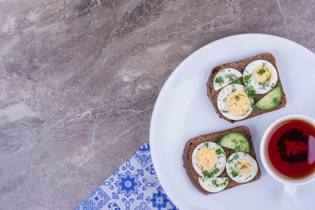 Broodjes met eieren en kruiden geserveerd met een kopje thee