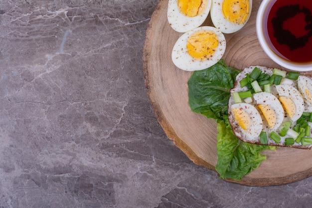 Broodjes met gekookte eieren en kruiden met een kopje thee.