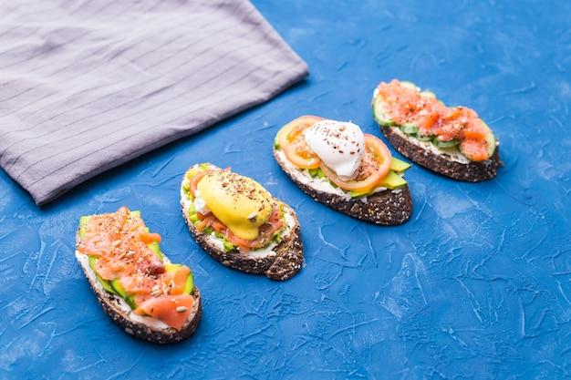 Broodjes met gerookte zalm, eieren, saus en avocado op blauwe ondergrond. concept van ontbijt en