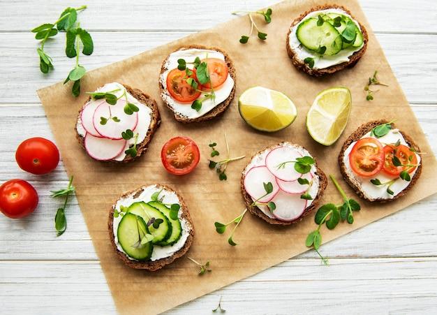 Broodjes met gezonde groenten en micro groenen op een houten tafel