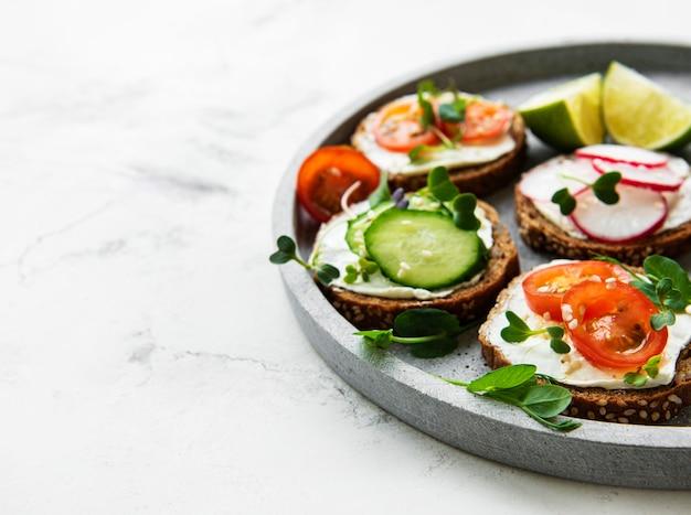 Broodjes met gezonde groenten en microgreens op wit