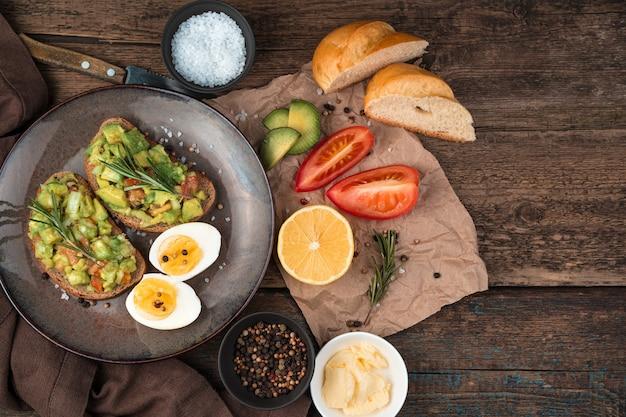 Broodjes met guacamole, tomaten, rozemarijn, citroen, boter op een houten achtergrond. bovenaanzicht met kopie ruimte. het concept van gezonde voeding.