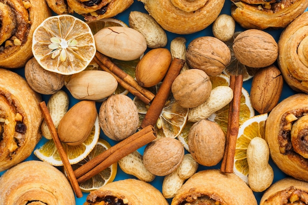 Broodjes met kaneel, noten en rozijnen en andere ingrediënten op een blauwe achtergrond, close-up.