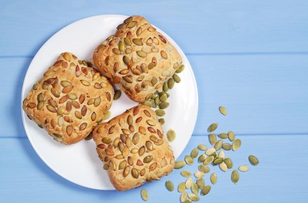 Broodjes met pompoenpitten in plaat op blauwe houten tafel