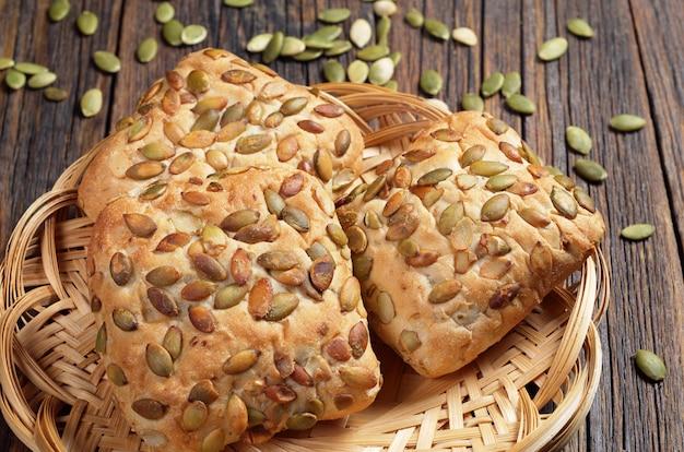 Broodjes met pompoenpitten op rieten plaat op de oude houten tafel