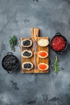 Broodjes met rode en zwarte kaviaar stokbrood, op grijze tafel, bovenaanzicht plat lag
